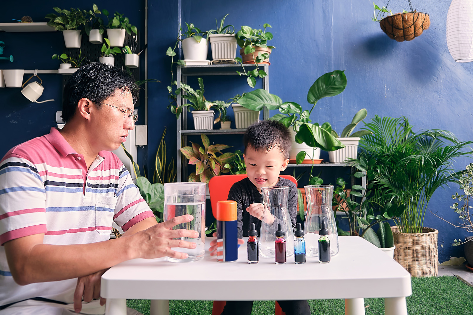 Parent sitting homeschooling with little kid, Father and son having fun preparing easy science experiment