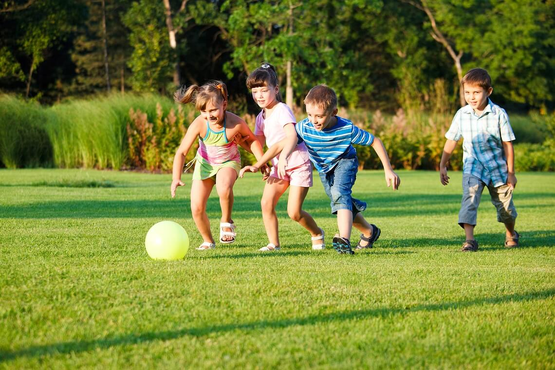 Four preschool kids playing with the ball